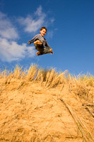 Boy jumping off sand dunes